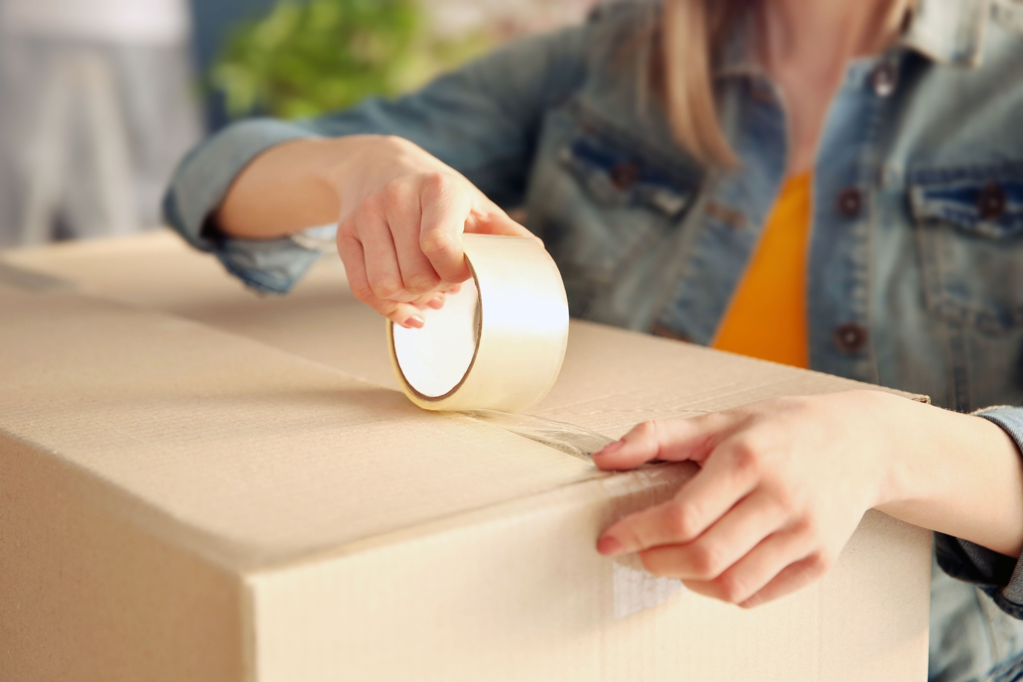 Young girl sealing with tape big cardboard box